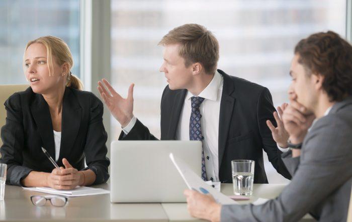 Tre personer som har en konflikt. En av männen försöker påverka en kvinna som tittar bort och ser besvärad ut.